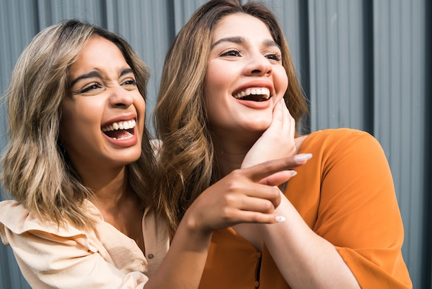 Portrait of two young friends spending good time together and having fun while standing outdoors. urban concept.