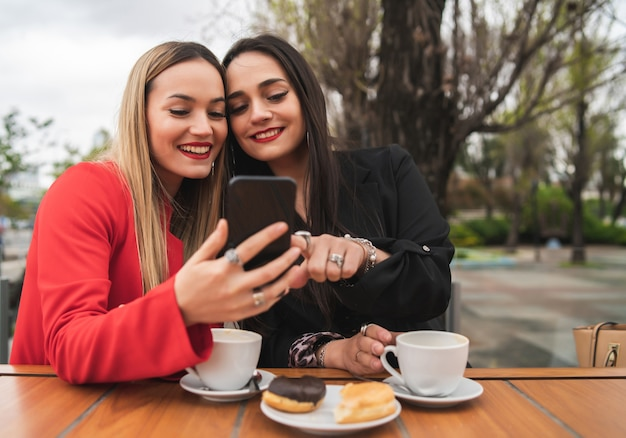 Portrait of two young friends using their mobile phone while sitting at coffee shop. lifestyle and friendship concept.