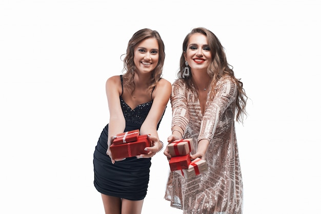 Portrait of two young girls giving you presents isolated on white