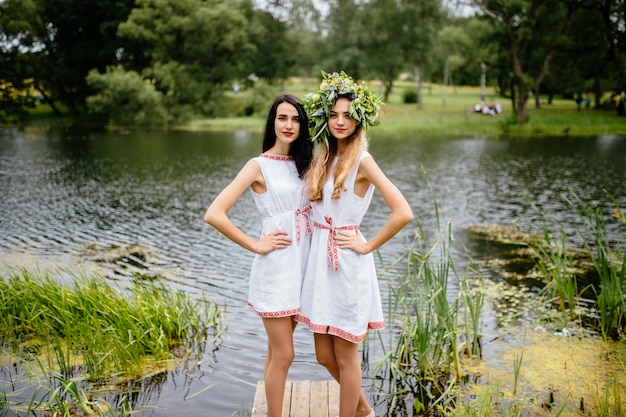 Portrait of  two young girls in traditional slavic dress with wreath of summer flowers. ethnic folk style friends in traditional costumes posing near lake.