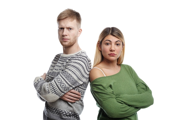 Portrait of two young male and female parents of caucasian appearance standing with arms folded, looking angrily, displeased with bad behavior of their little son