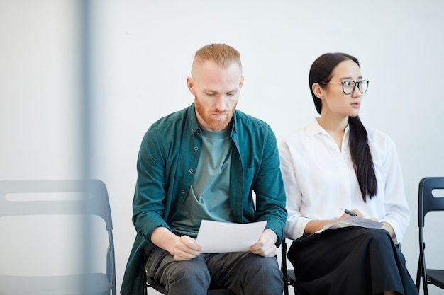 Portrait of two young people waiting in line for job interview and reviewing notes , copy space