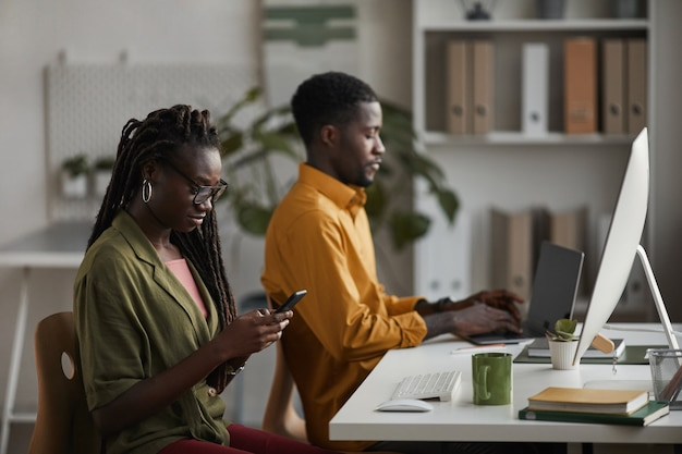 Portrait of two young people working in office, focus on elegant african-american woman using smartphone in foreground