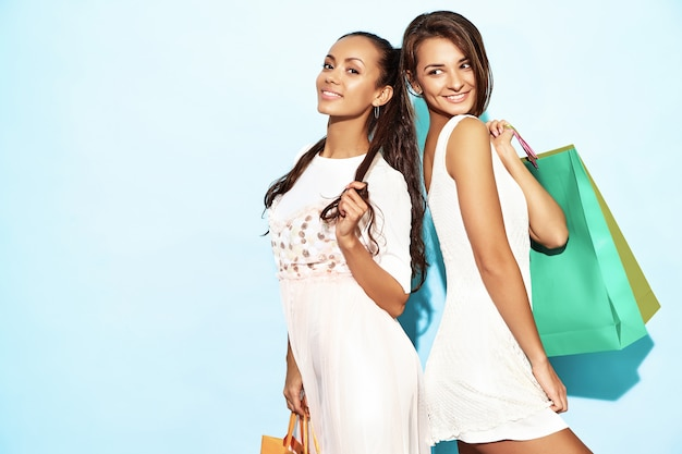 Portrait of two young sexy stylish smiling brunette women holding shopping bags. hot women dressed in summer hipster clothes. positive models posing over blue wall