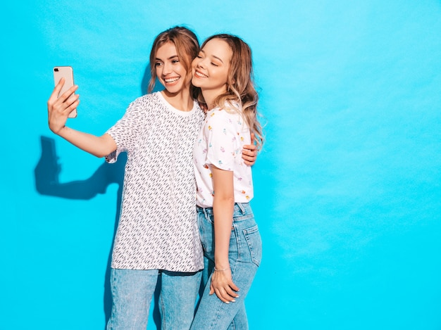 Portrait of two young stylish smiling blond women. girls dressed in summer hipster clothes. positive models making selfie on smartphone near blue wall in studio