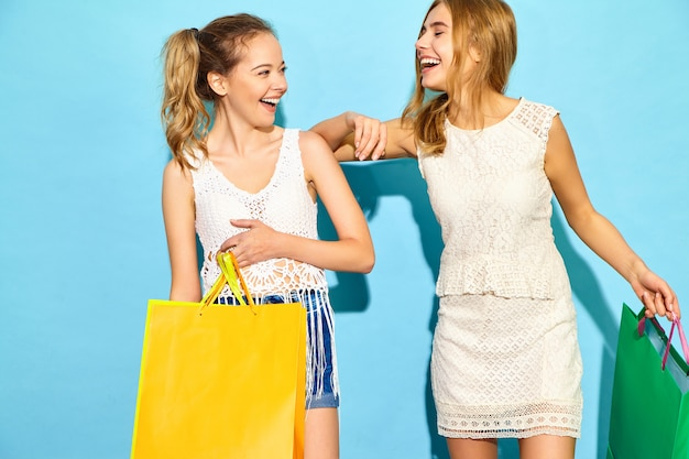 Portrait of two young stylish smiling blond women holding shopping bags. women dressed in summer hipster clothes. positive models posing over blue blackground