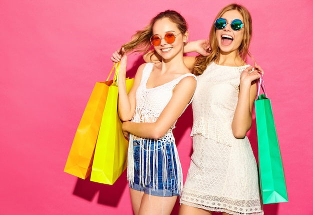 Portrait of two young stylish smiling blond women holding shopping bags. women dressed in summer hipster clothes. positive models posing over pink blackground