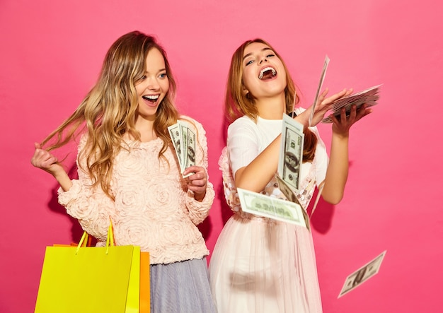 Portrait of two young stylish smiling blond women holding shopping bags. women dressed in summer hipster clothes. positive models spending money over pink wall