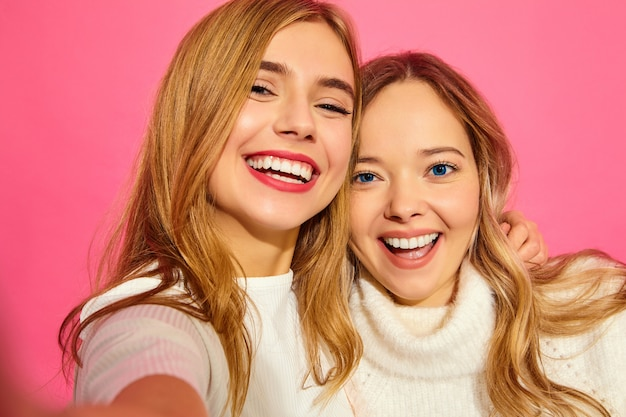Portrait of two young stylish smiling blond women
