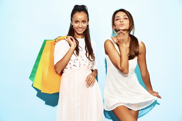 Portrait of two young stylish smiling brunette women holding shopping bags. women dressed in summer hipster clothes. positive models posing over blue wall and giving air kiss