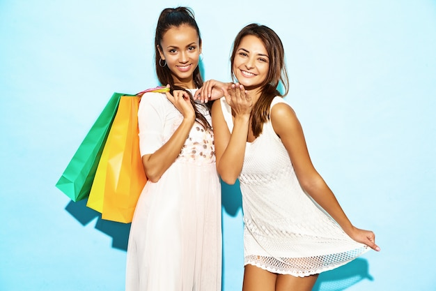 Portrait of two young stylish smiling brunette women holding shopping bags. women dressed in summer hipster clothes. positive models posing over blue wall