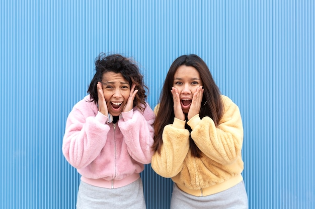 Portrait of two young women on a blue background they have their hands on their faces and are screaming in fear. concept of terror, surprise or panic. space for text.