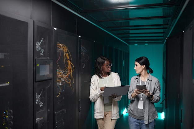 Portrait of two young women using laptop in server room while setting up supercomputer network, copy space