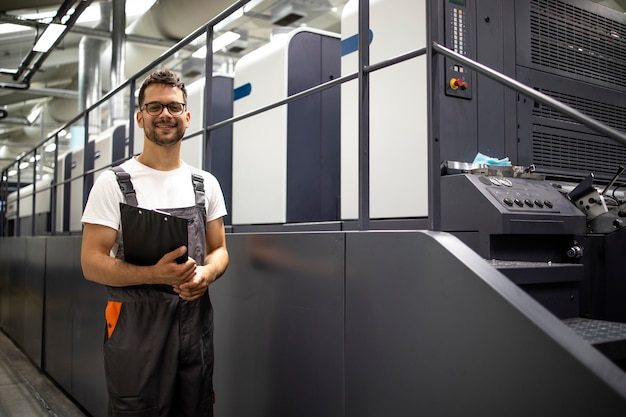 Portrait of typographer standing by modern offset printing machine controlling process of print