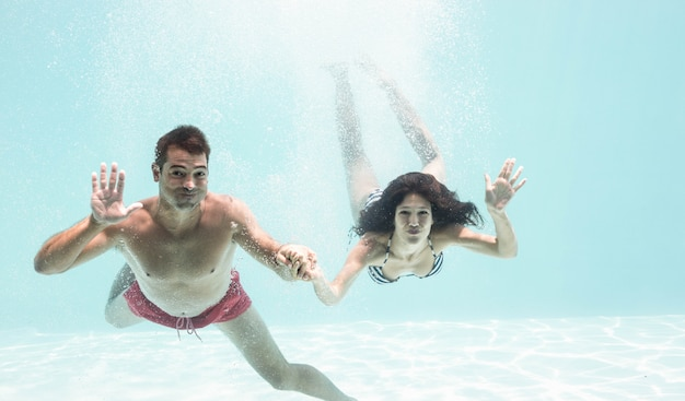 Portrait of underwater couple holding hands and enjoying in swimming pool