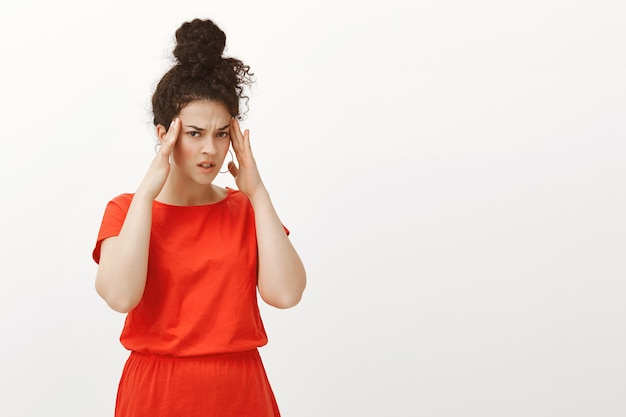 Portrait of unfocused troubled caucasian woman in red dress, holding hands on temples and frowning from displeasure