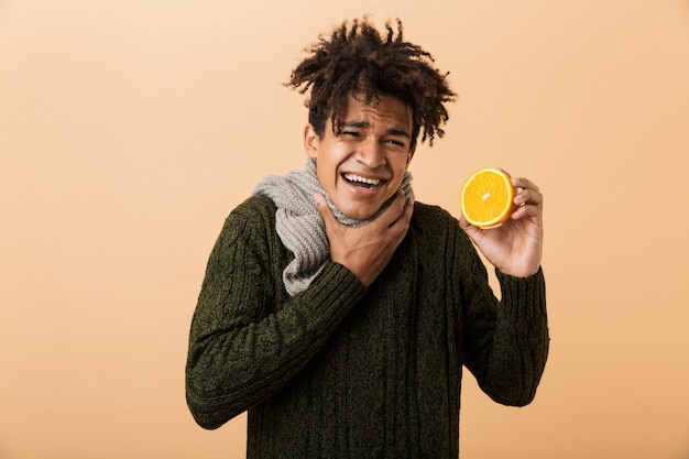 Portrait of unhappy african american guy wearing sweater and scarf touching throat and holding half an orange, isolated over beige wall