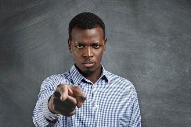 Portrait of unhappy african boss having mad expression pointing his index finger, looking angrily and frowning as if accusing or blaming you for mistake. selective focus on man's face