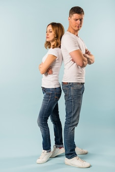 Portrait of unhappy angry young couple standing back to back not speaking to each other after an argument