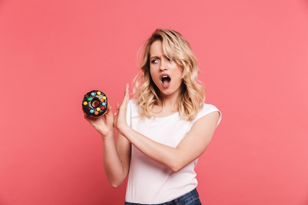 Portrait of unhappy blond woman wearing casual t-shirt doing stop gesture while holding tasty sweet donut isolated over pink wall