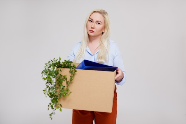 Portrait of unhappy business woman holding cardboard box after getting fired from her job, copy space over gray background