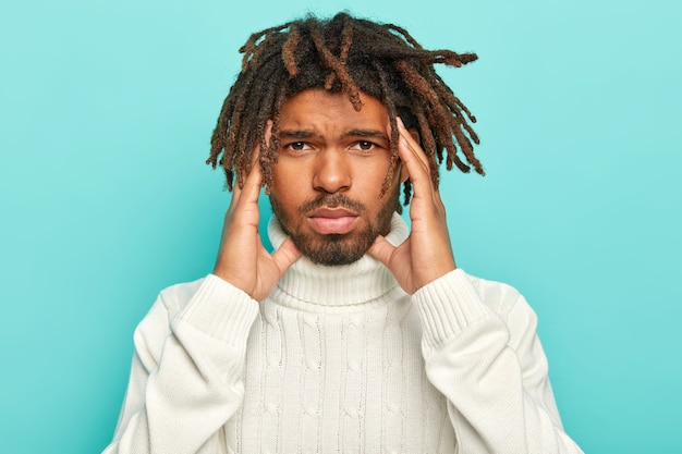 Portrait of unhappy dark skinned man with dreads, suffers from unbearable headahce, keeps hands on temples, wears white sweater with collar, isolated over blue background, asks for painkillers