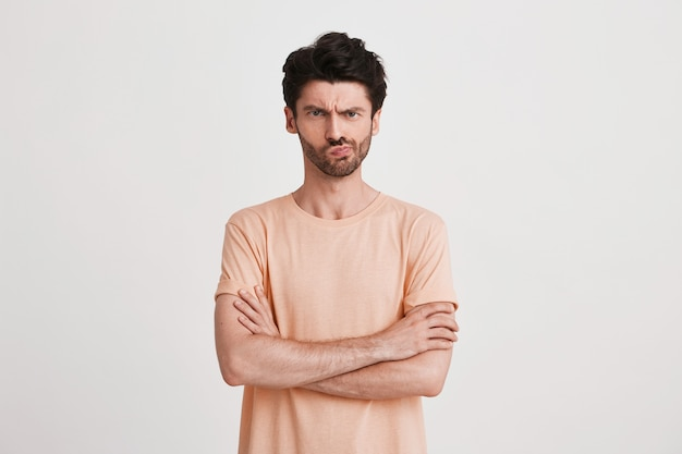 Portrait of unhappy displeased young man with bristle wears peach t shirt looks upset and points to the side with finger isolated on white