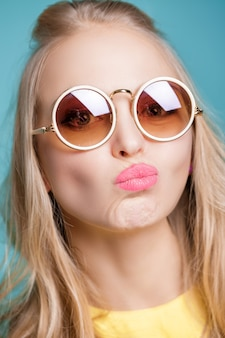 Portrait of unhappy and frustrated blond woman in sunglasses and yellow shirt on blue background