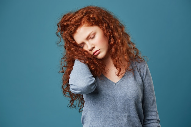 Portrait of unhappy frustrated woman with red wavy hair and freckles holding hand in hair with closed eyes having migraine or headache.
