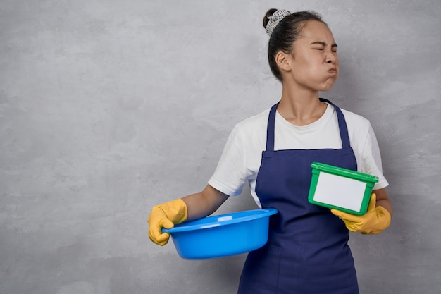 Portrait of unhappy housewife or maid woman in uniform holding basin and green plastic box with washing capsules, making unsatisfied face while standing against grey wall. housekeeping, housework