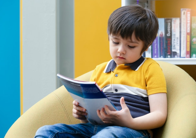 Portrait of unhappy kid sitting alone looking at the book with bored face in library, upset chile boy with sad face with deep through sitting alone in book shop, little boy with bored face