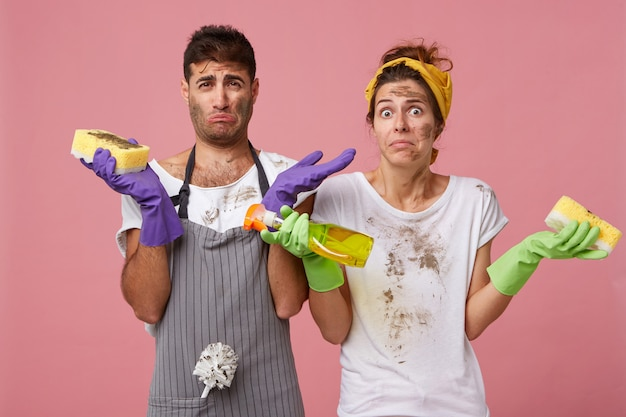 Portrait of unhappy male and female with dirty faces and clothes holding washing spray and sponges shrugging shoulders being sad not knowing how to remove all stains on windows. facial expressions