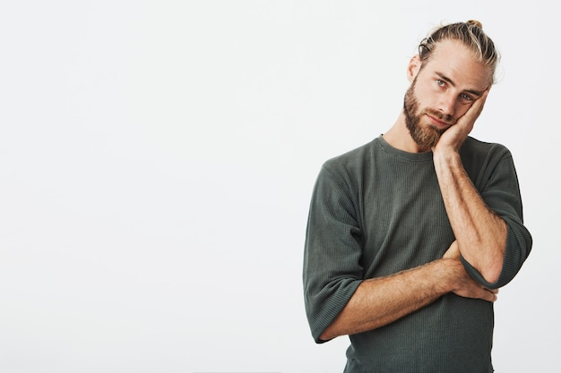 Portrait of unhappy mature bearded guy in grey shirt holding hand on cheek exhausted and tired