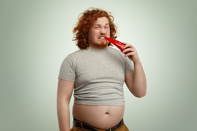 Portrait of unhappy overweight caucasian man with big belly trying red pepper having disgusted expression on his face while forced to keep strict vegetable diet, fighting against excess weight