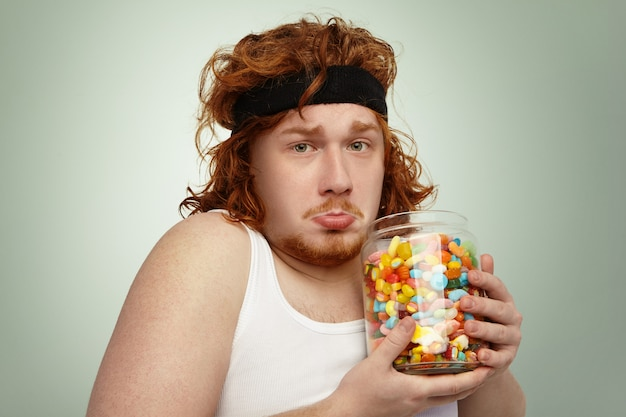 Portrait of unhappy overweight obese young red-haired european man wearing hairband and white tank top after physical exercises, feeling frustrated while can't stop consuming delicious sweets