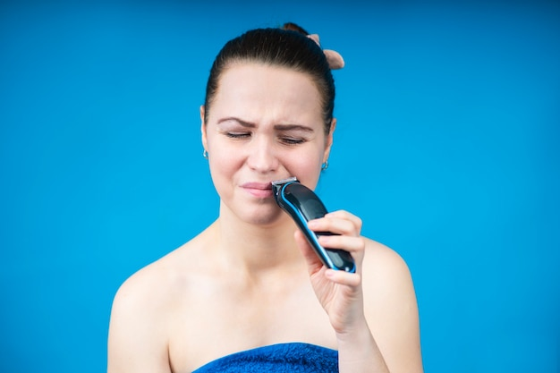 Portrait of unhappy sad girl, young beautiful woman depilating removing hair from her face, shaving