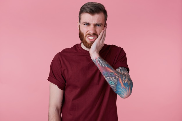 Portrait of unhappy young bearded guy with tattooed hand, touching mouth with hand with painful expression because of toothache or dental illness on teeth.