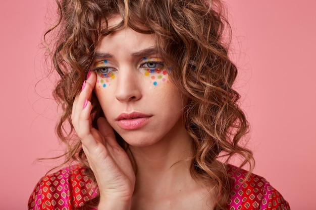 Portrait of unhappy young curly woman with festive makeup touching gently her face and looking away with empty eyes, posing in colored patterned top