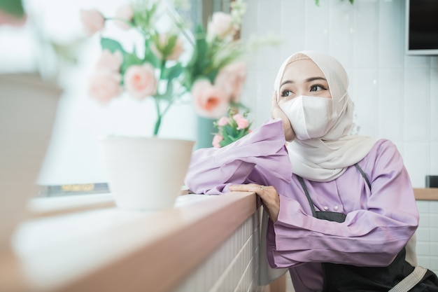 Portrait of unhappy young muslim woman wear mask while looking out the window