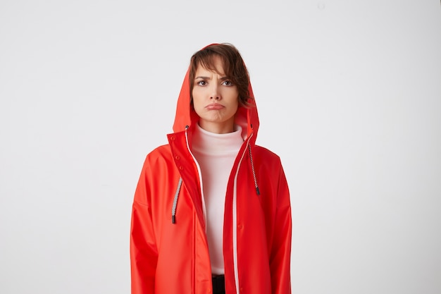 Portrait of unhappy young nice happy short haired lady in red rain coat, sadly looks with lips down. something wrong. stands.