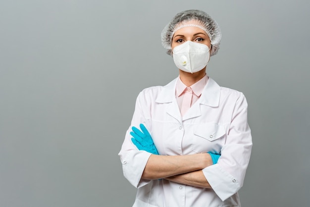 Portrait of an unhappy young woman doctor in a medical mask on a gray background the doctors tired