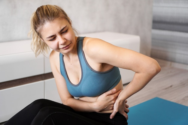 Portrait of unhappy young woman sitting on yoga mat, touching her back after training, suffering from backache, feeling pain, side view