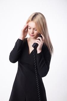 Портрет несчастной молодой женщины разговаривает по телефону, глядя вниз, изолированные на белом