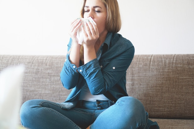 Portrait of unhealthy cute blonde female with napkin blowing nose, looks to the source of the allergy. rhinitis, cold, allergy concept