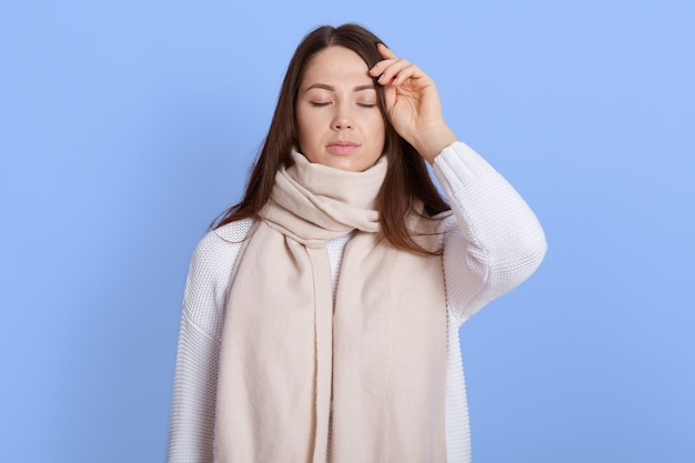 Portrait of unhealthy woman wrapped in warm white scarf, touching her head, suffering headache, fever and flu symptoms, keeping eyes closed, isolated on lilac wall.
