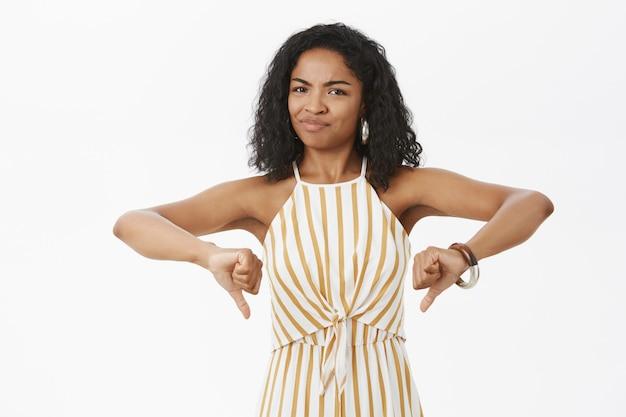 Ritratto di donna dalla pelle scura prepotente insoddisfatta insoddisfatta con l'acconciatura riccia in tuta elegante gialla sorridendo e mostrando i pollici verso il basso