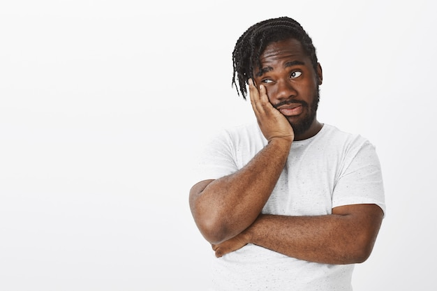 Portrait of unimpressed guy with braids posing against the white wall