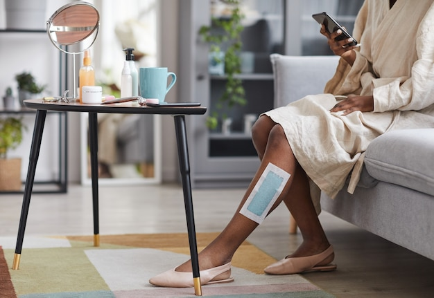 Portrait of unrecognizable african-american woman enjoying beauty routine at home with focus on wax strips on leg, copy space