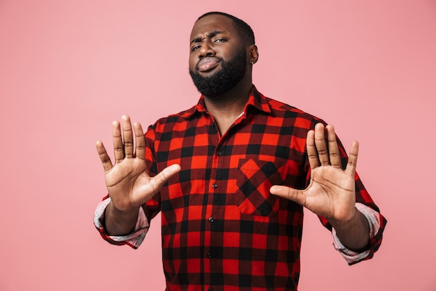 Portrait of an unsatisfied african man wearing plaid shirt standing isolated over pink wall, showing stop gesture