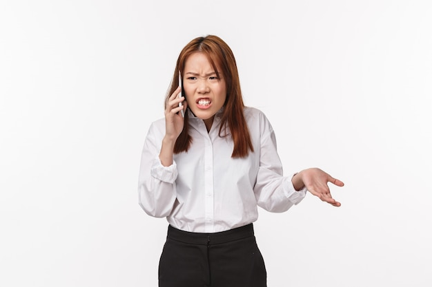 Portrait of unsatisfied angry asian woman talking on phone, grimacing upset and outraged, having tough serious conversation, argument with partner, standing pissed-off